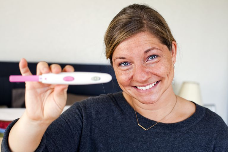 Pregnancy test held by happy woman