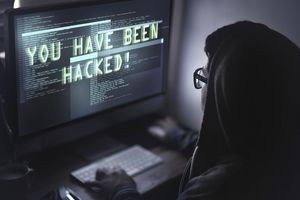 """Woman at computer with """"you have been hacked"""" on the screen"""