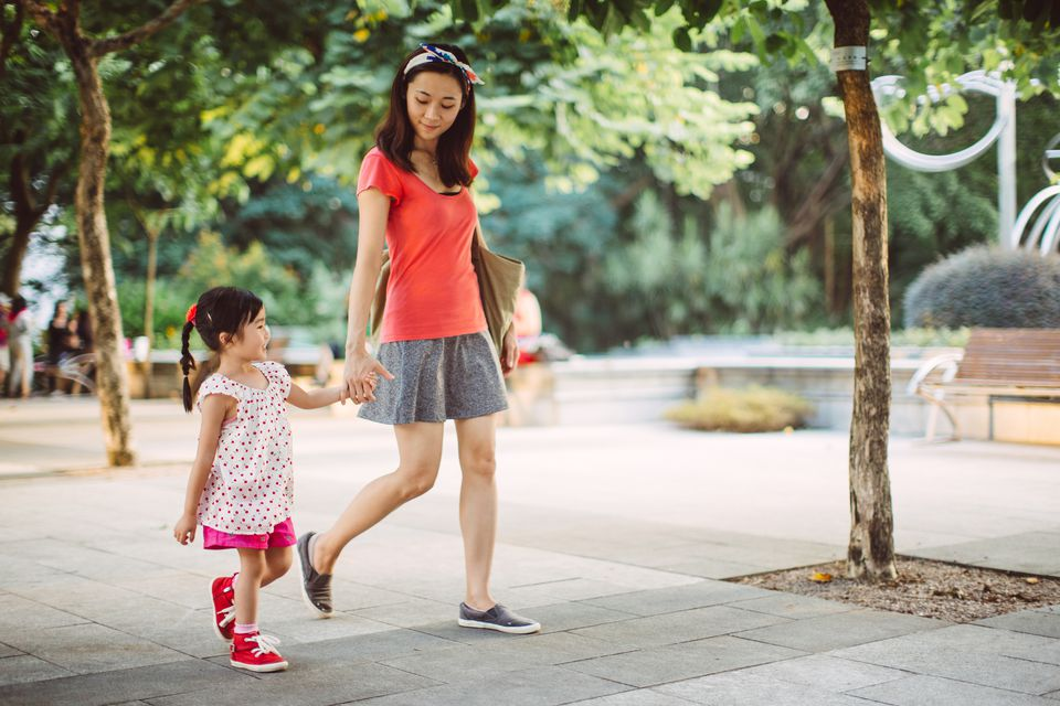 Mom & toddler strolling joyfully in park