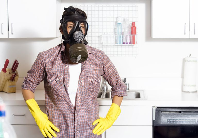 woman in gas mask and cleaning gloves