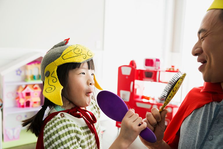 Father and daughter in costumes singing into hairbrushes
