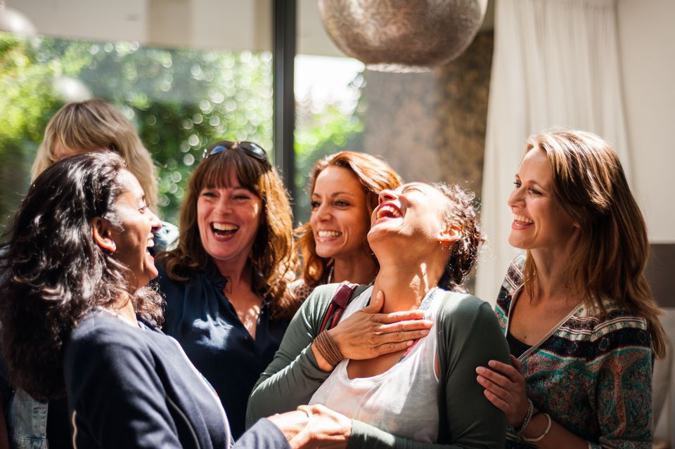Women at reunion greeting and smiling