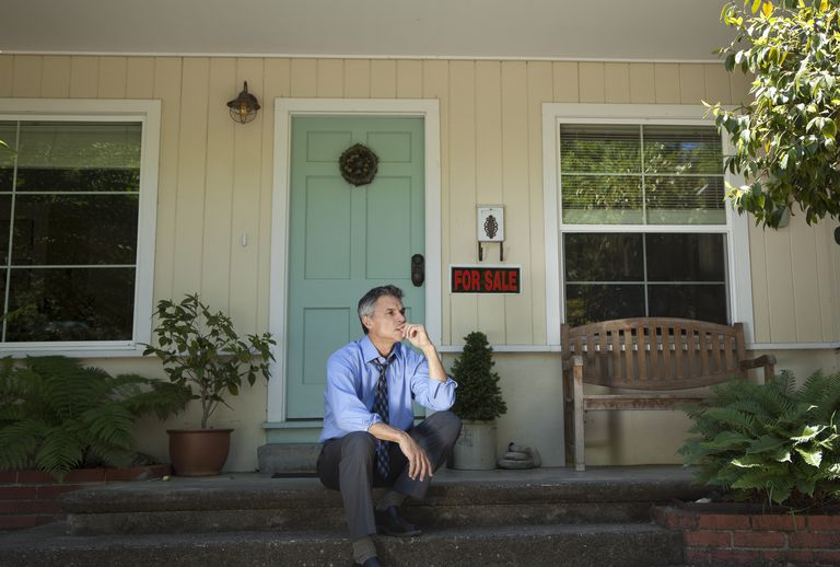 man sitting on house stoop with for sale sign behind him