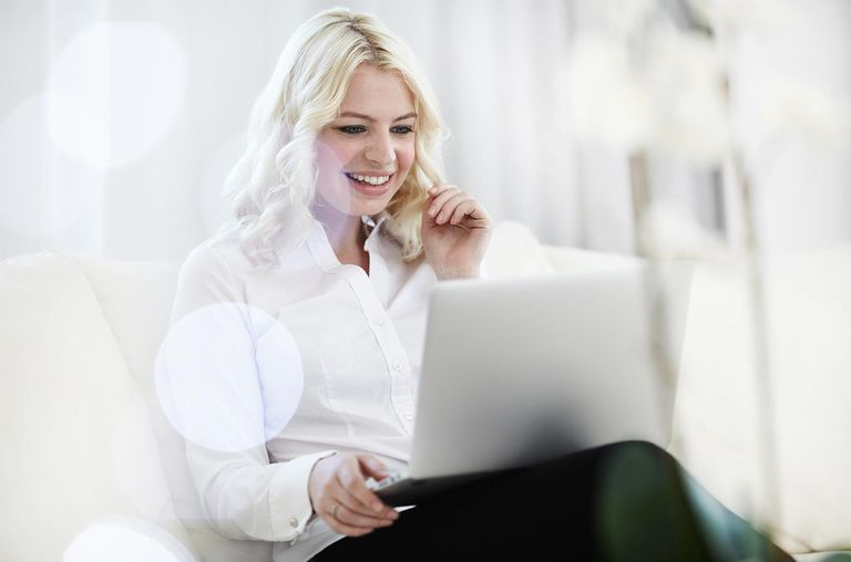 Young Adult woman using laptop on sofa