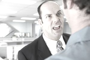 Mature businessman yelling at coworker in office