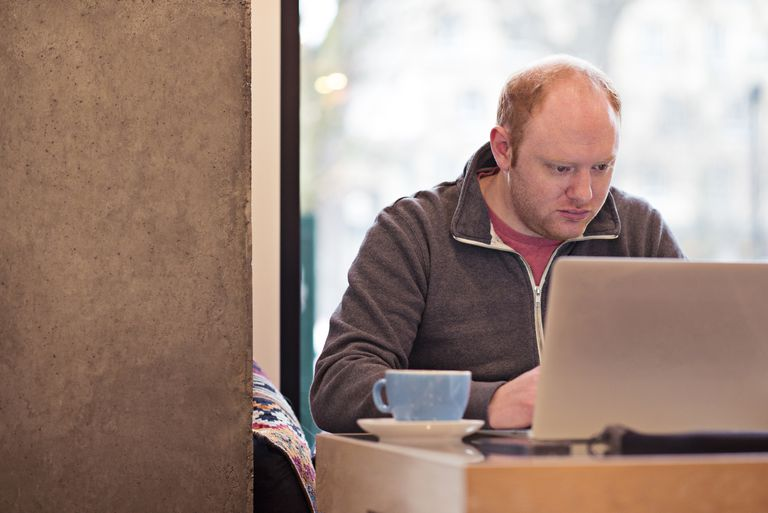 Man in cafe works on laptop