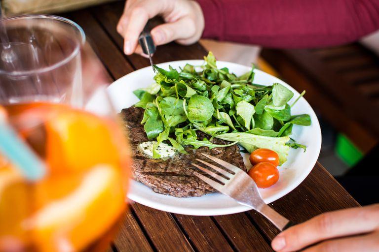 Man eating steak and salad