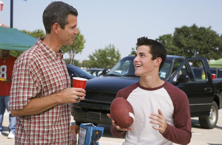 Father and teen son (13-15) at tailgate party.