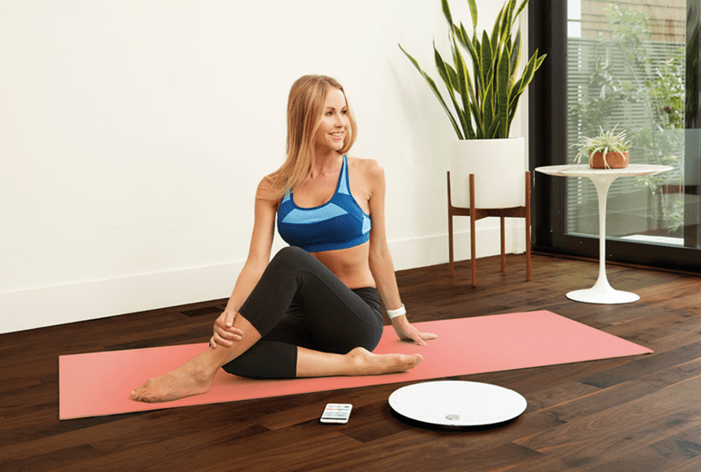 Woman doing yoga using smart scale to track health.