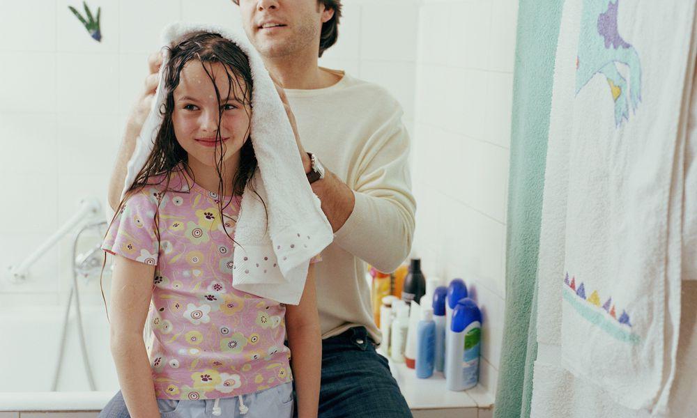 Dad drying daughters hair