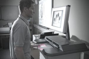 Man scanning fingerprint on machine with screen in laboratory