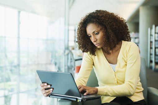 USA, Utah, Salt Lake City, Portrait of young woman using laptop