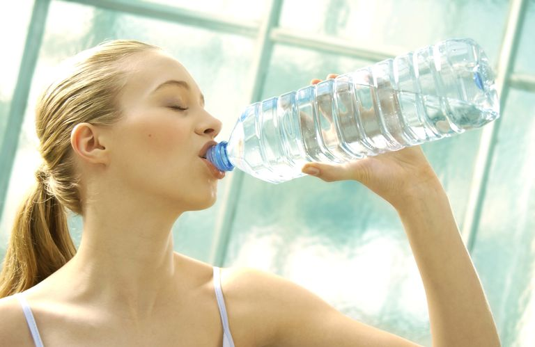 Woman drinking out of a big water bottle
