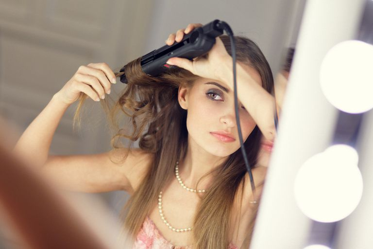 girl using curling iron