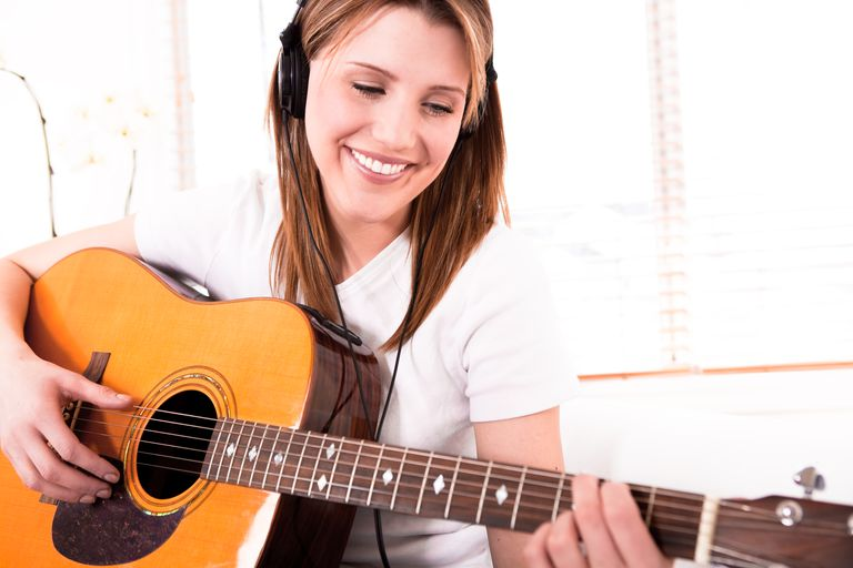 Smiling young woman playing the guitar