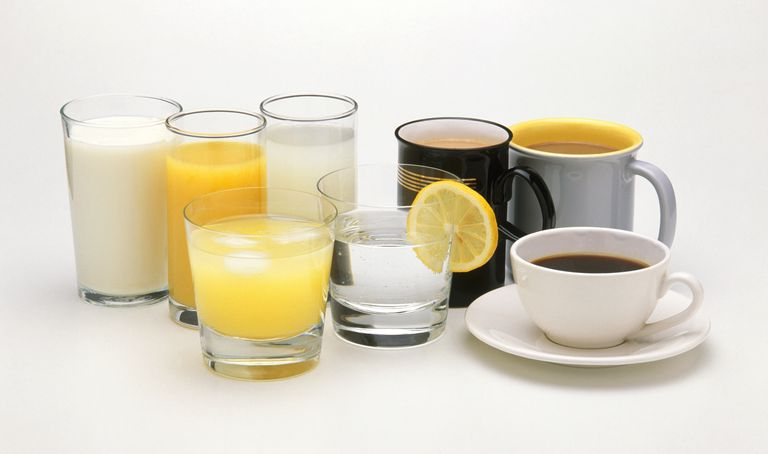 Mugs and cup of tea and coffee next to glasses of water, milk and fruit juice