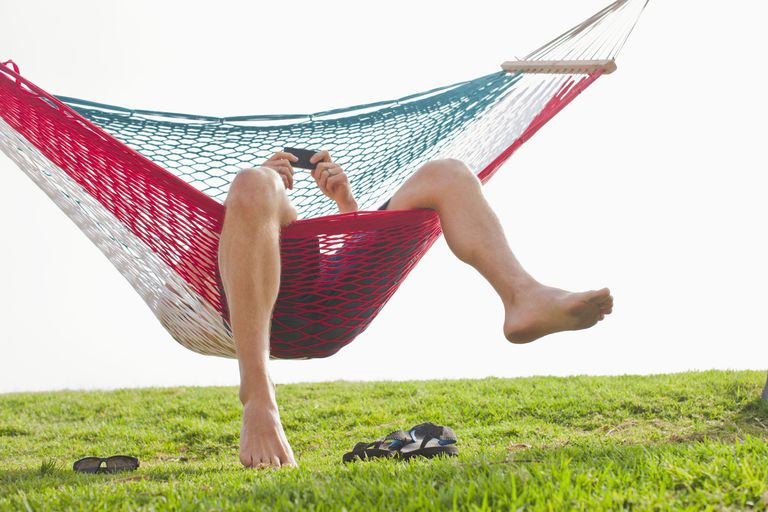 Caucasian man relaxing in hammock with cell phone