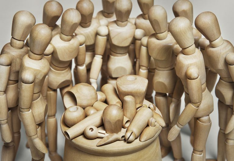 Many wood mannequins looking at one in pieces