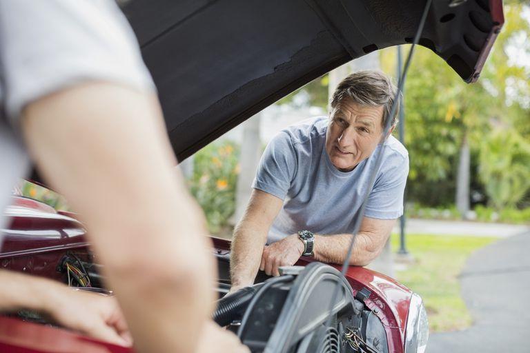 Senior men repairing car engine
