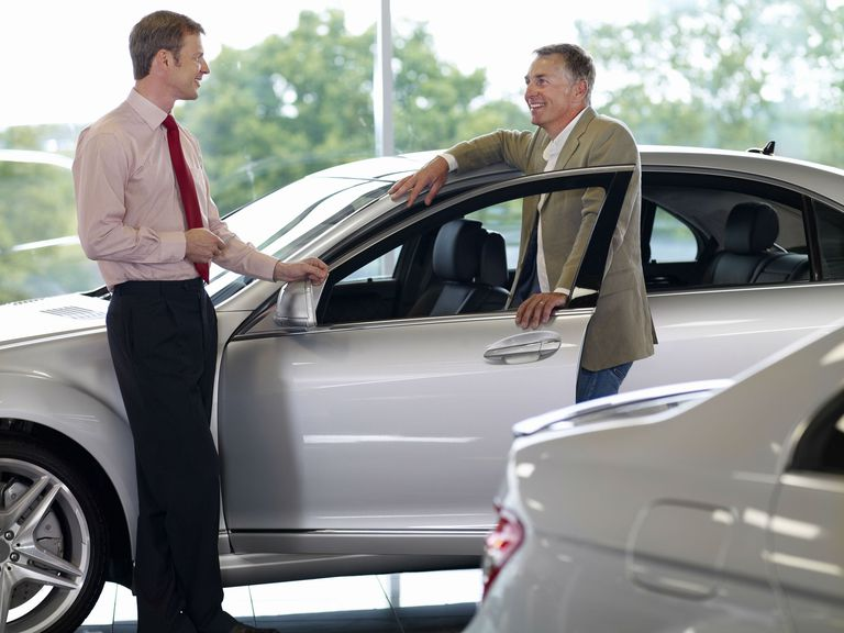 Salesman talking man in automobile showroom