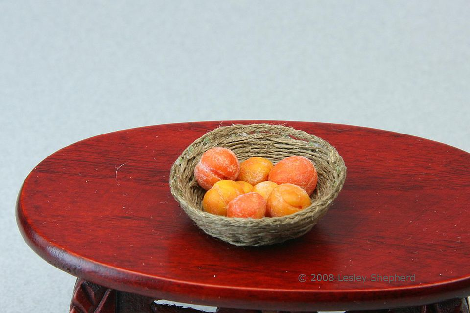 A finished woven fruit basket in dolls house scale made from wire and embroidery thread.
