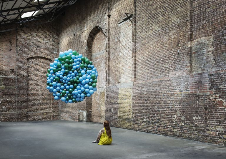 Woman in warehouse with globe made of balloons