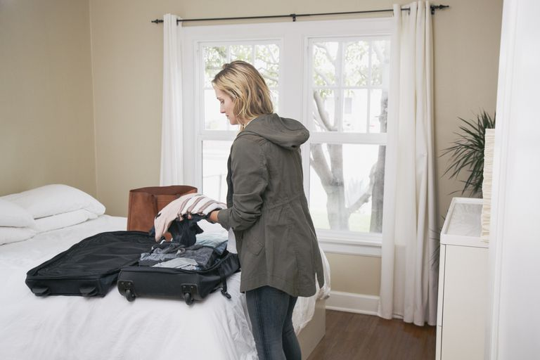 Woman unpacks suitcase