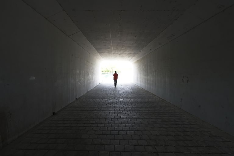 silhouette of person walking out of a tunnel. Light at End of Tunnel