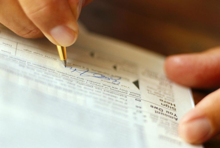 Man signing tax form that contains a taxable IRA distribution.