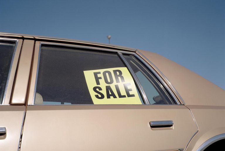 'For Sale' sign placed in car window, outdoors close-up