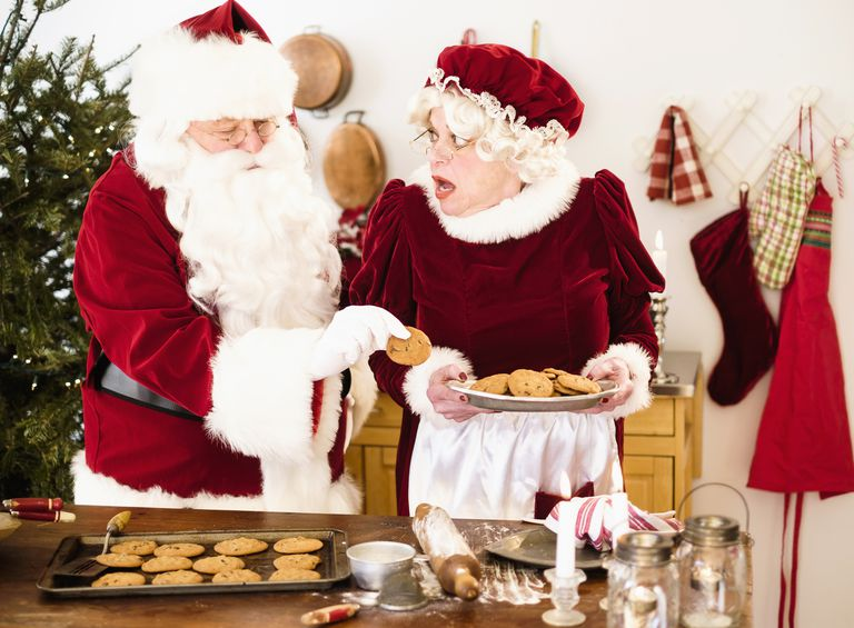 Santa stealing gingerbread cookie from Mrs. Claus