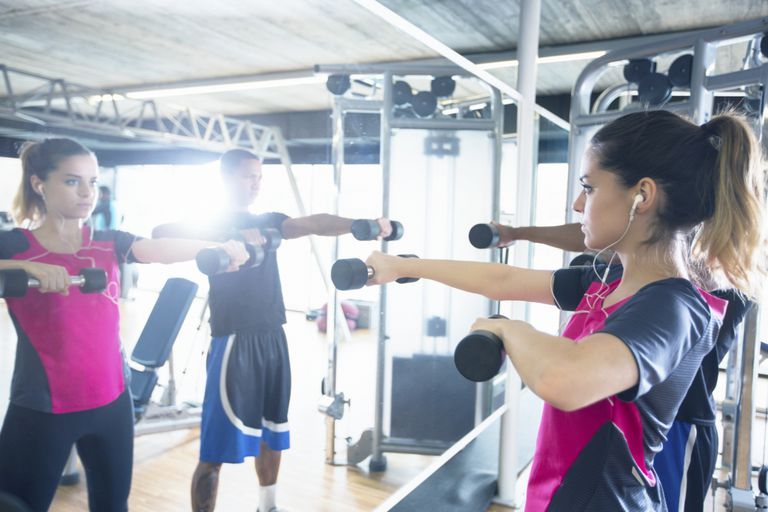 Man and woman lifting weights in front of mirror