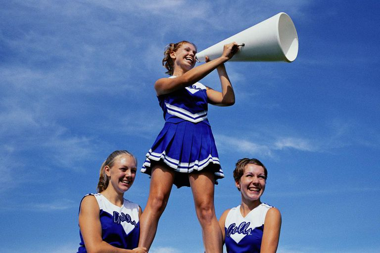 Two cheerleaders supporting third cheerleader with megaphone