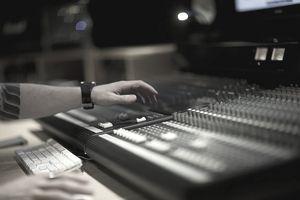 Hand on mixing desk in recording studio