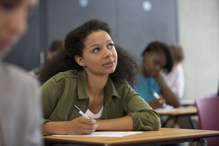 young woman thinking while writing at classroom desk