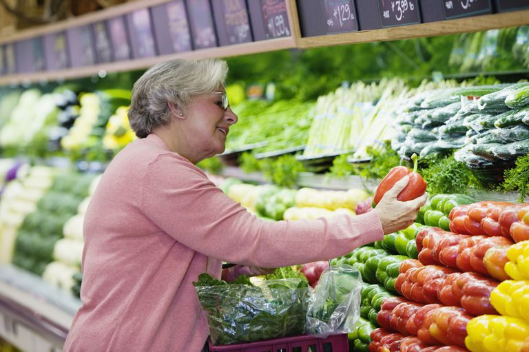 'Woman looking at peppers in grocery store, smiling'
