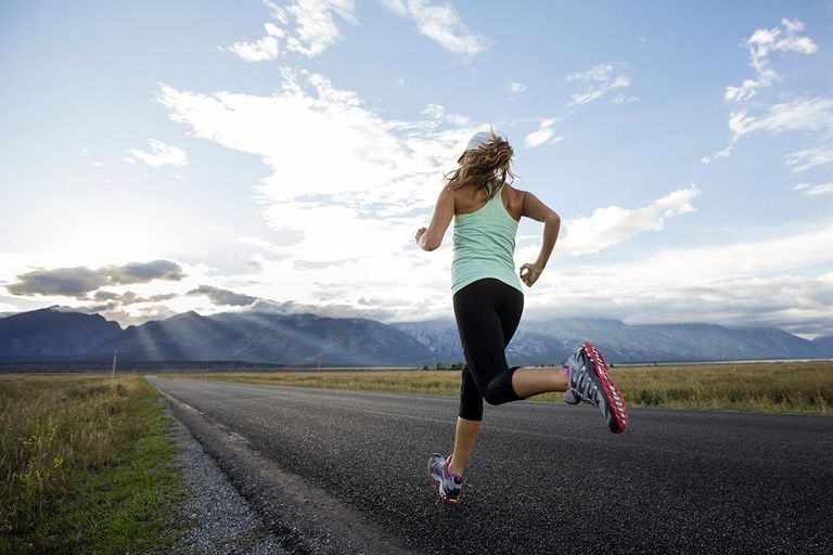 A woman running near the Teton mountains in Jackson Hole, Wyoming.