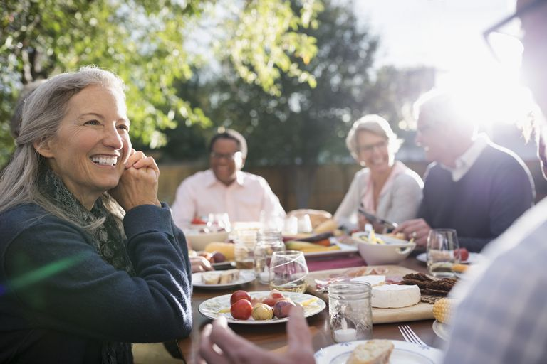 Smiling senior woman talking to friend at garden party lunch at sunny patio table