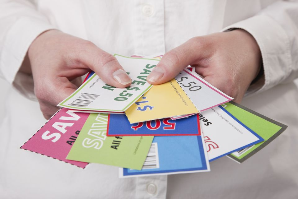 Woman holding printable coupons from Savings Angel.