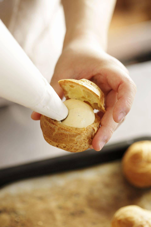 Woman squeezing custard cream into Cream Puff