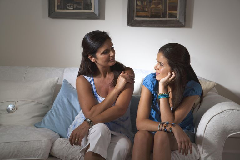 Mother and teenage daughter on sofa