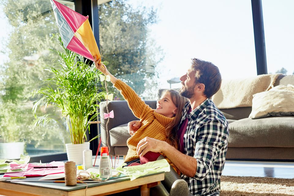 father and daughter making kite