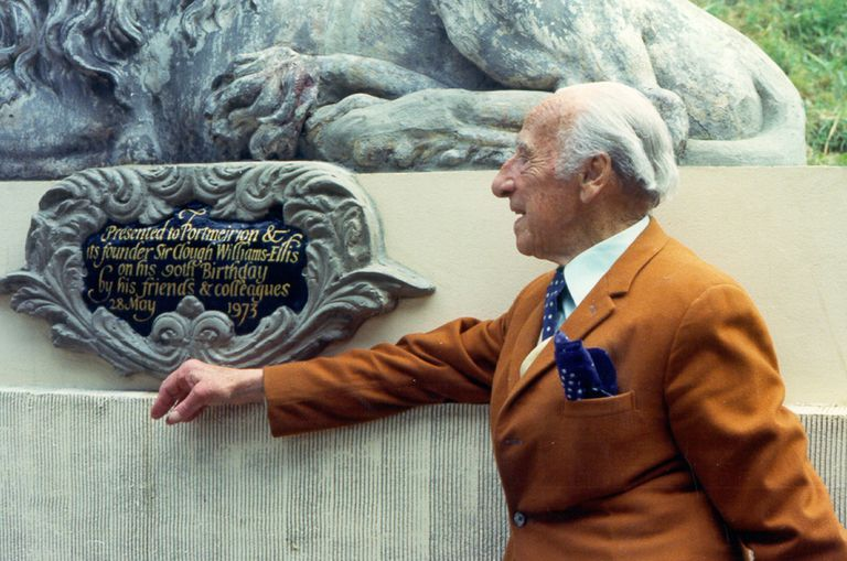 white-haired man in orange-brown suit looking at a plaque with ornate cast-iron framing