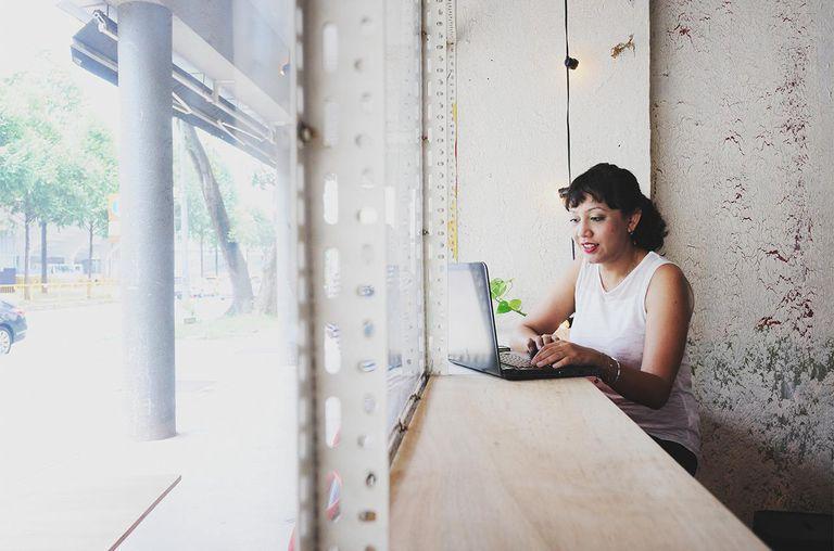 Woman working on laptop in window