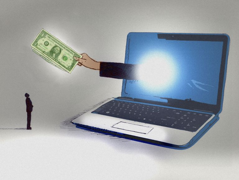 Businessman looking up at hand emerging from computer screen holding dollar bills