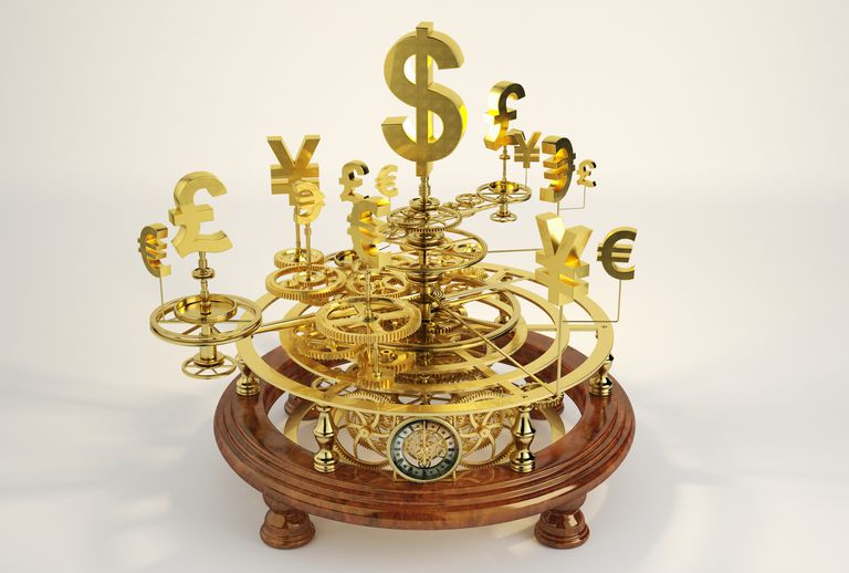 Gold international currency symbols on clockwork orrery
