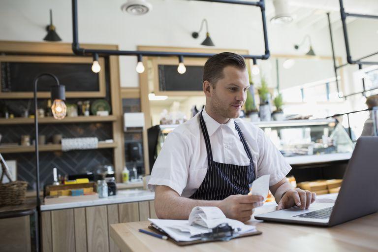 Market owner inputting receipts on laptop