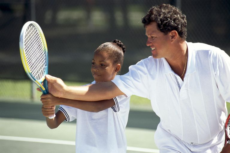 Man showing a young girl tennis techniques