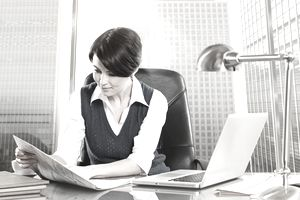 Business woman reading newspaper in office