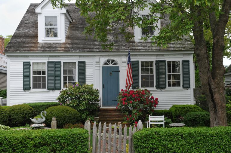 White cape cod style house with shutters dormers and fanlight